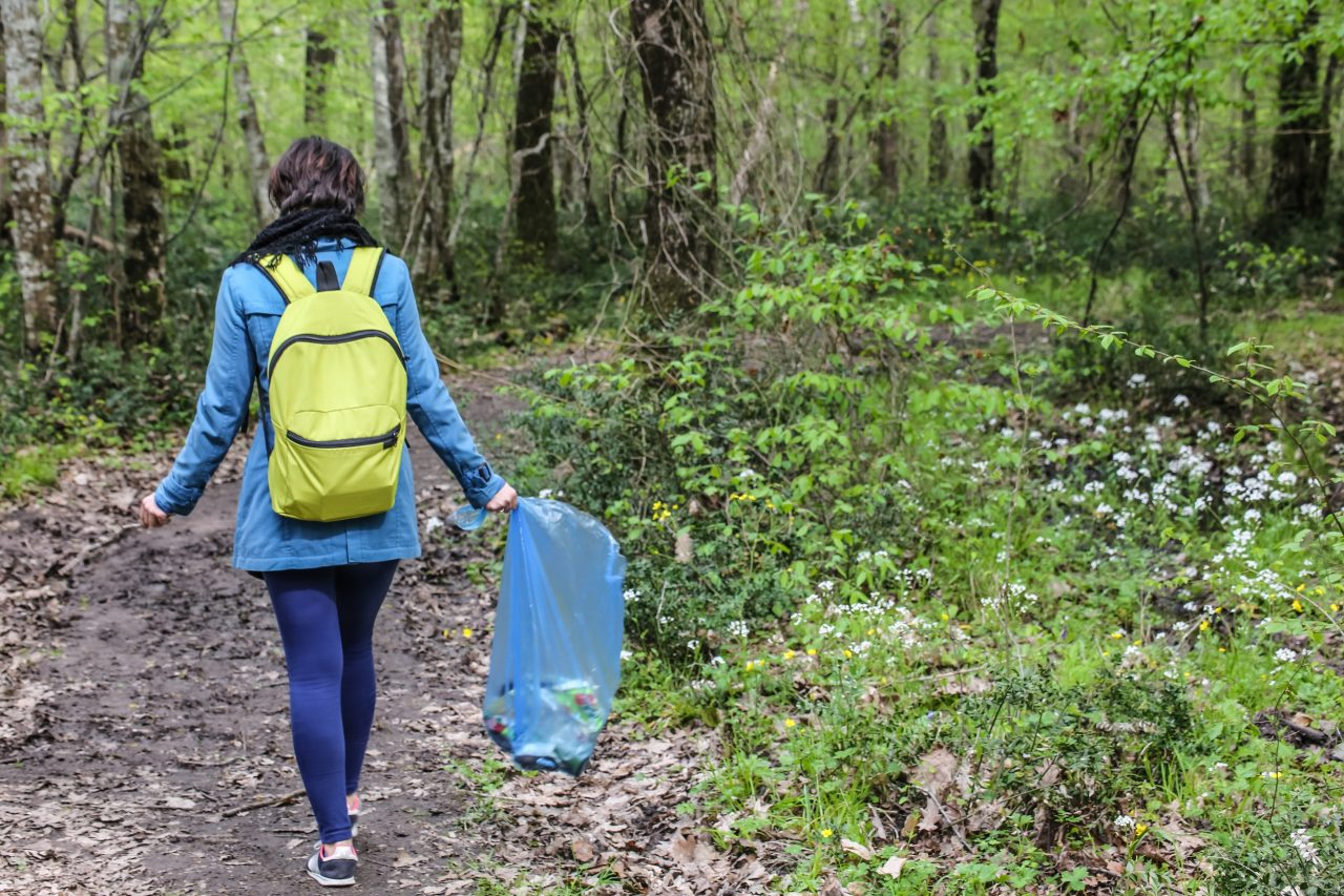 Environmental activist collecting plastic garbages in nature