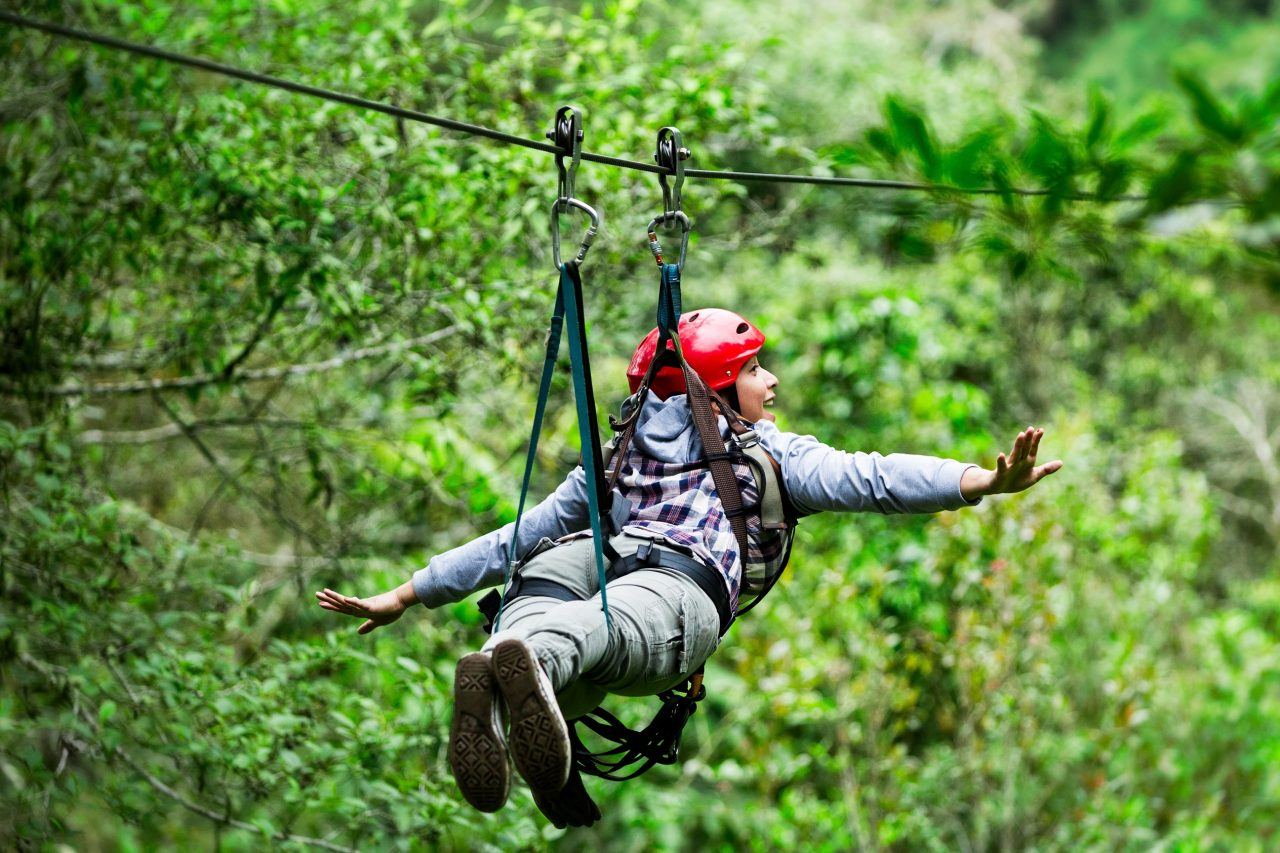 Adult tourist wearing casul clothing on zip line trip, selective focus against blured forest