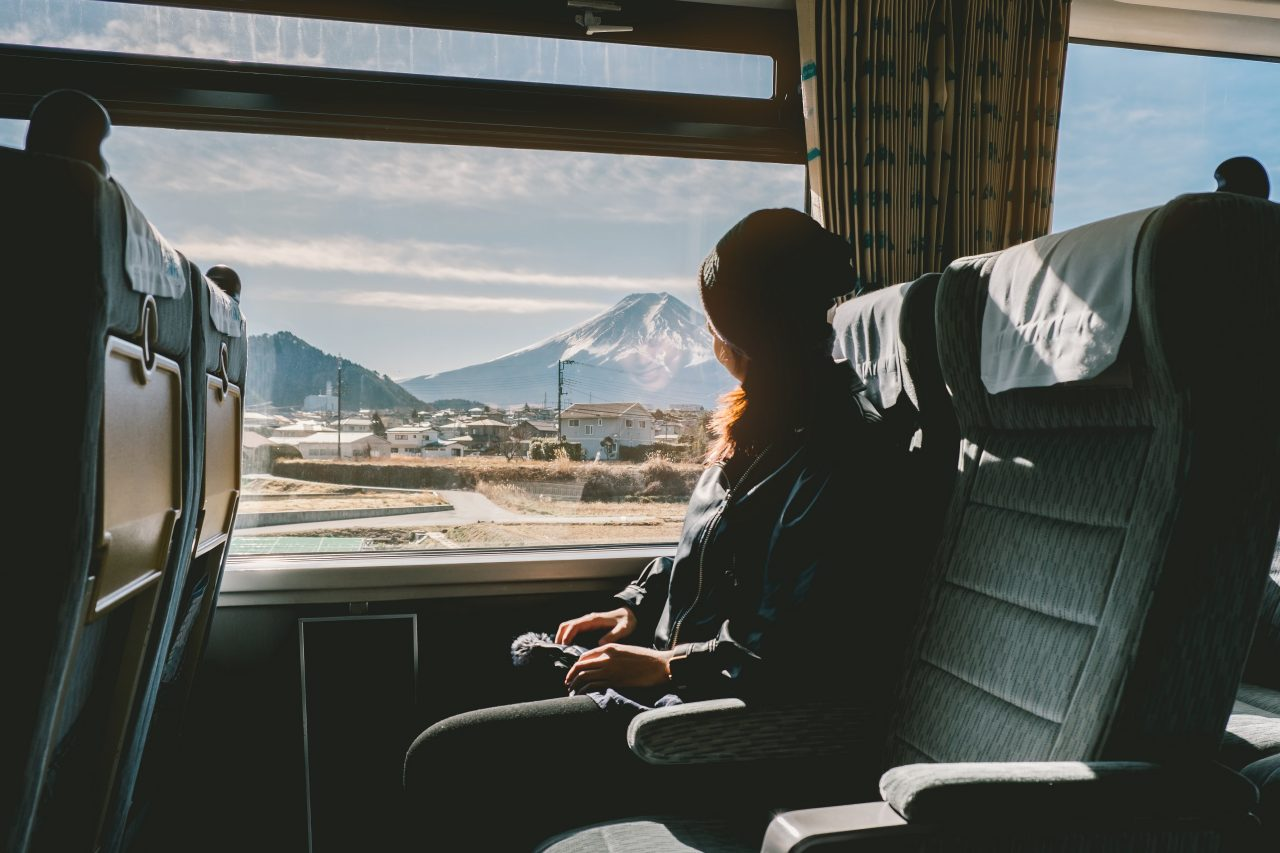 Enjoying travel. Young pretty woman traveling by the train from sitting near the window and looking mountain Fuji. vintage filter. Travel concept