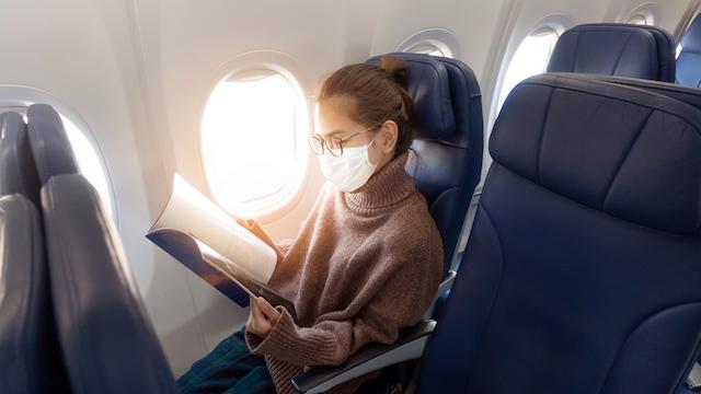 航空機の機内でマスクをする女性