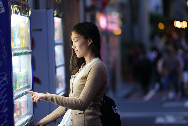 自動販売機で飲み物を買う女性
