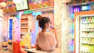 自動販売機の飲み物を飲む女性