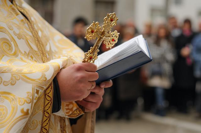 聖書と十字架を持つ祭司