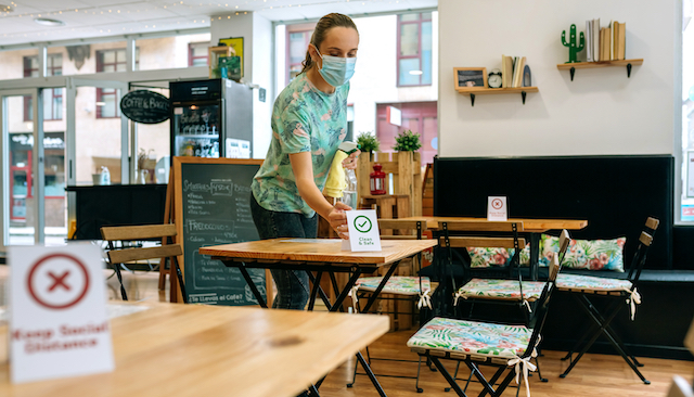 テーブルを拭くコーヒーショップの店員