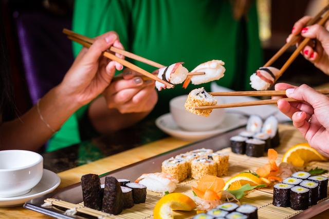 箸で寿司を食べる人たち